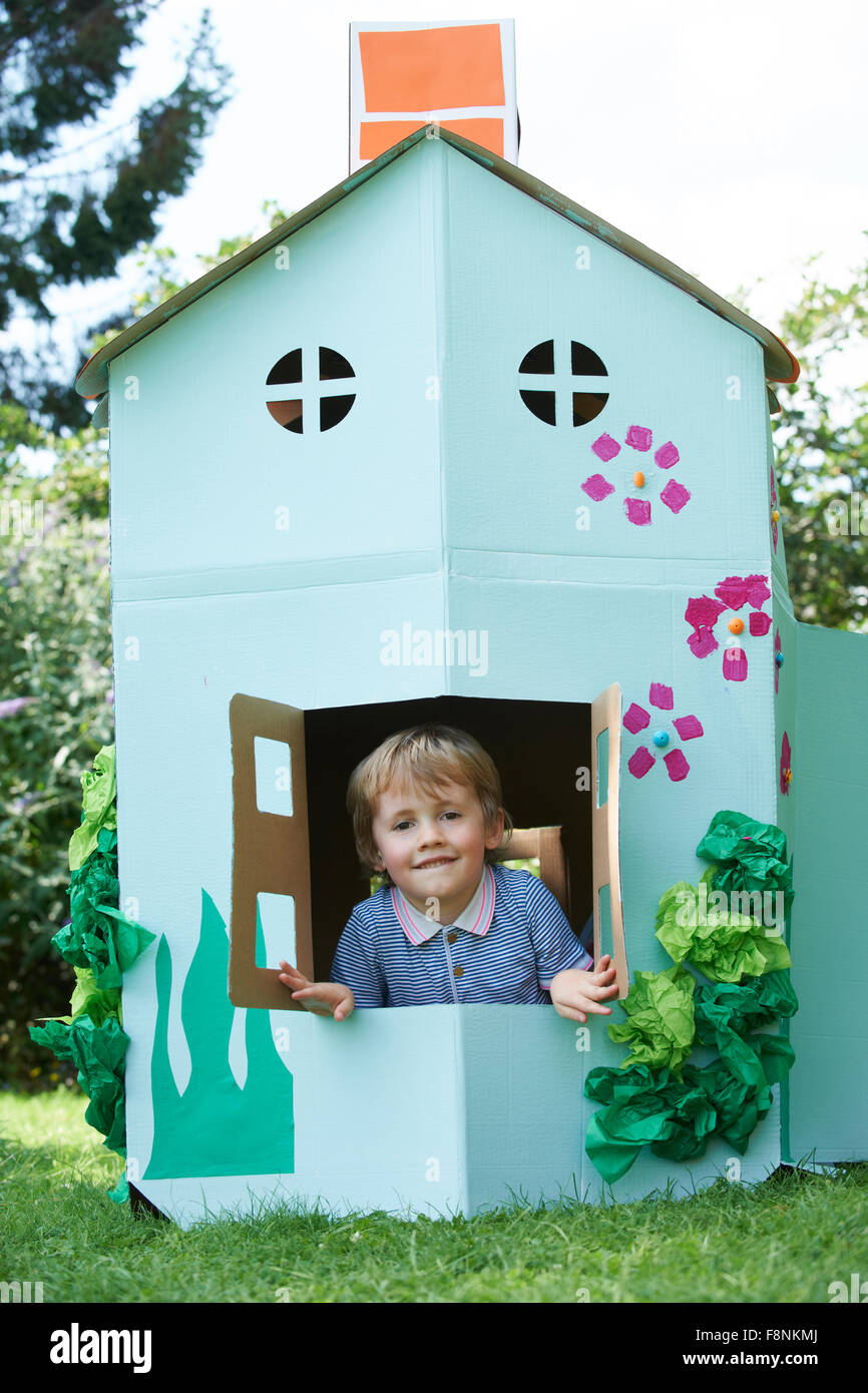 Young Boy Playing In Home Made Cardboard House - Stock Image