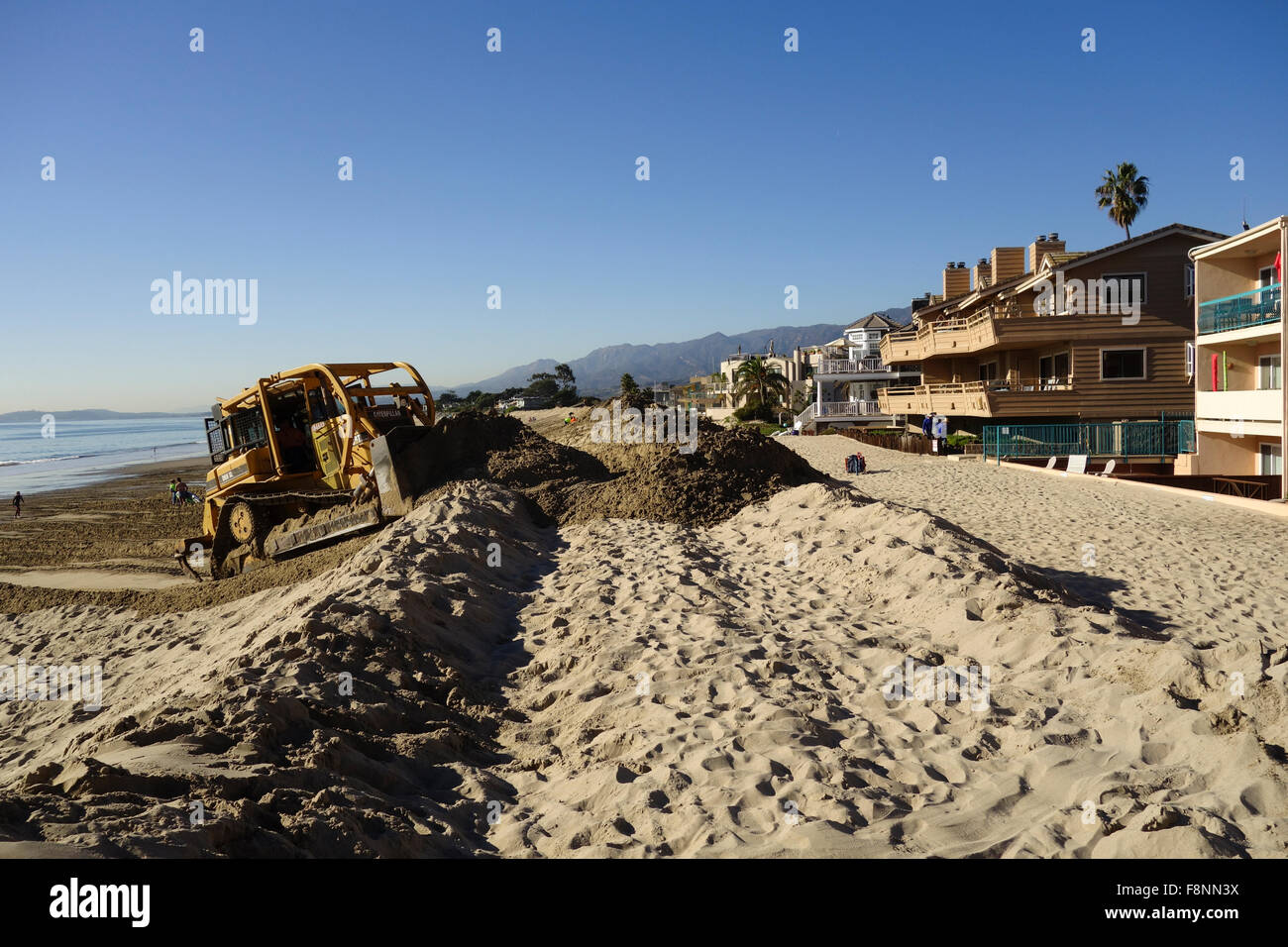 bulldozer builds sand berm to combat high tides and El Nino conditions on beach in Carpinteria Central California - Stock Image
