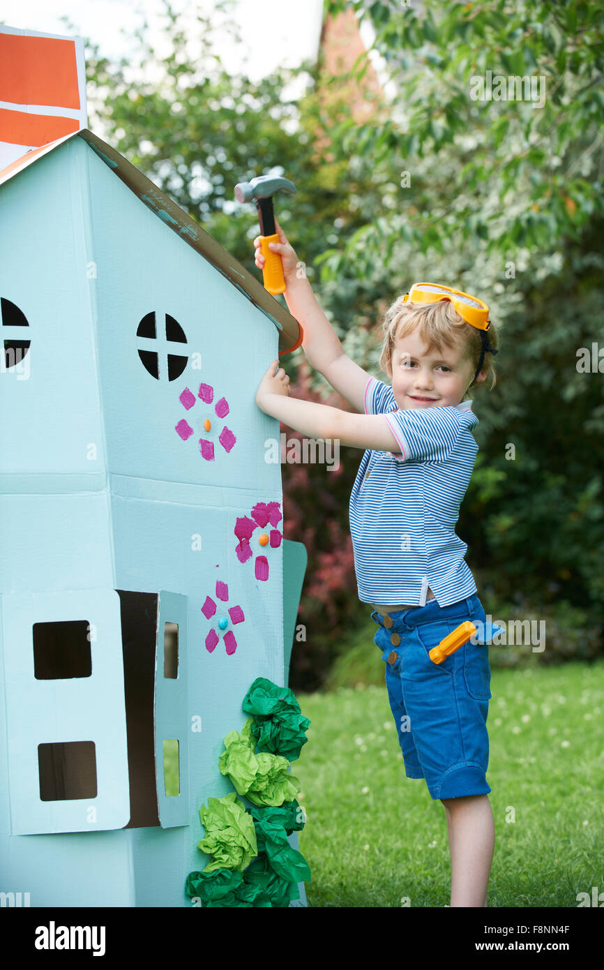 Young Boy Pretending To Fix Cardboard Playhouse - Stock Image