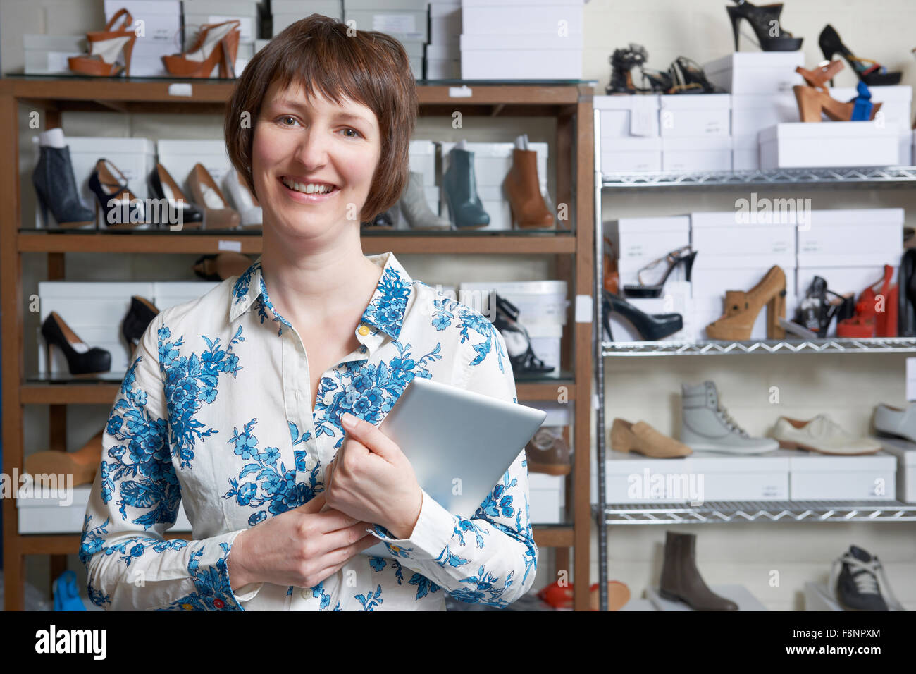 Owner Of Online Shoe Business Using Digital Tablet - Stock Image