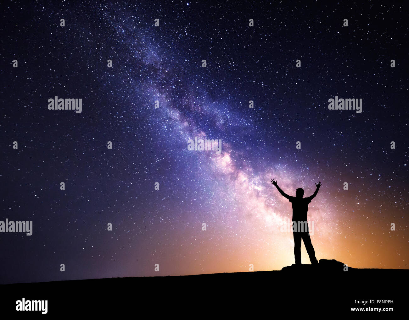 Milky Way. Night sky with stars and silhouette of a man with raised-up arms - Stock Image