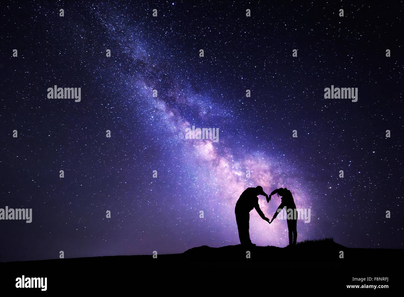 Man and woman holding hands in heart shape on the background of the Milky Way - Stock Image