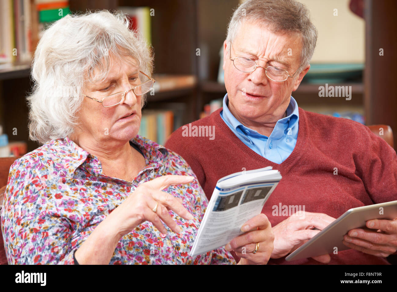 Confused Senior Couple Trying To Operate Mobile Phone - Stock Image