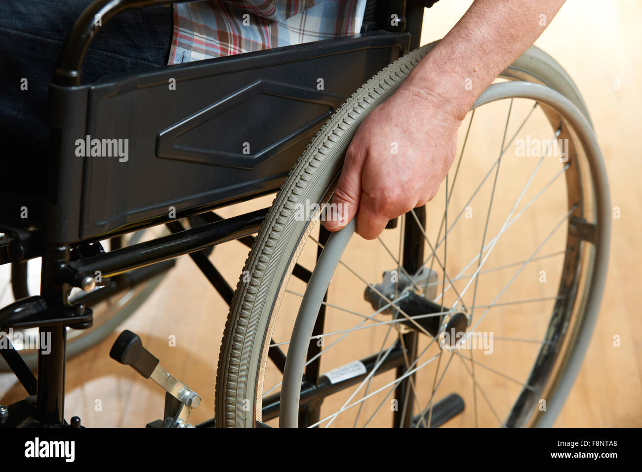 Close Up Of Man's Hands Pushing Wheelchair - Stock Image
