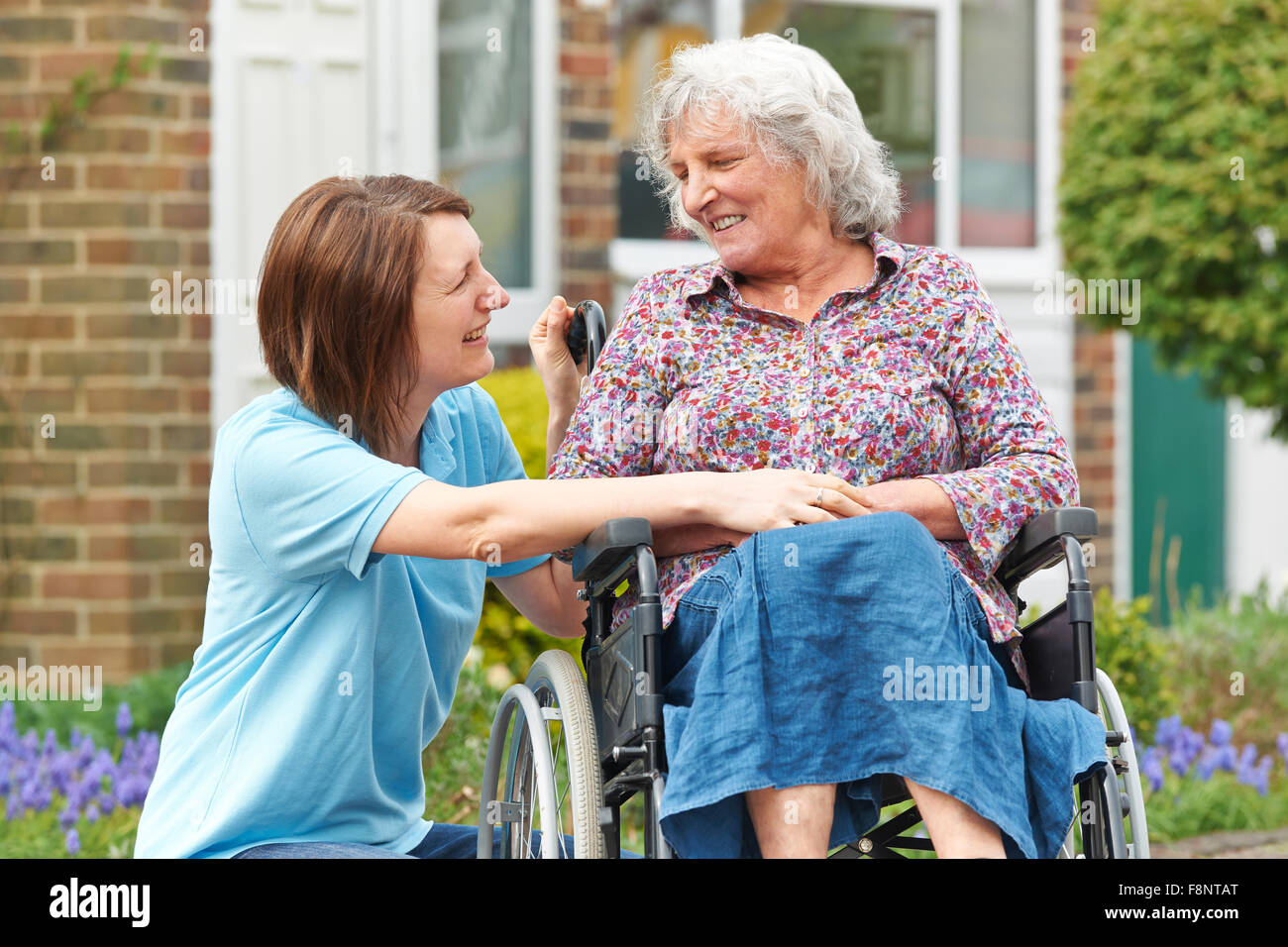 Carer With Senior Woman In Wheelchair - Stock Image