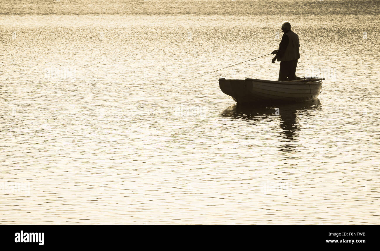 Man Fly fishing from boat on reservoir - Stock Image