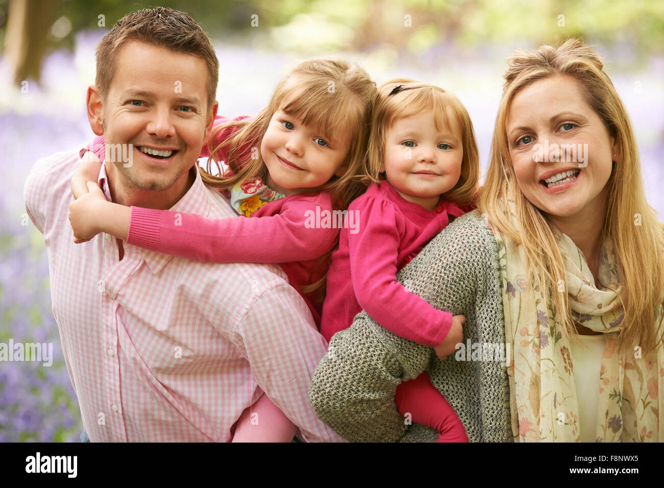 Family Walking Through Bluebell Woods Together Stock Photo