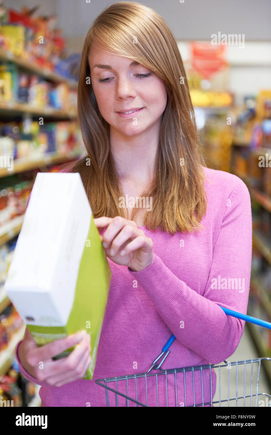 Woman Checking Labelling On Box In Supermarket - Stock Image