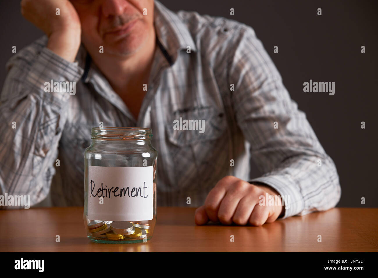 Depressed Man Looking At Empty Jar Labelled Retirement Stock Photo