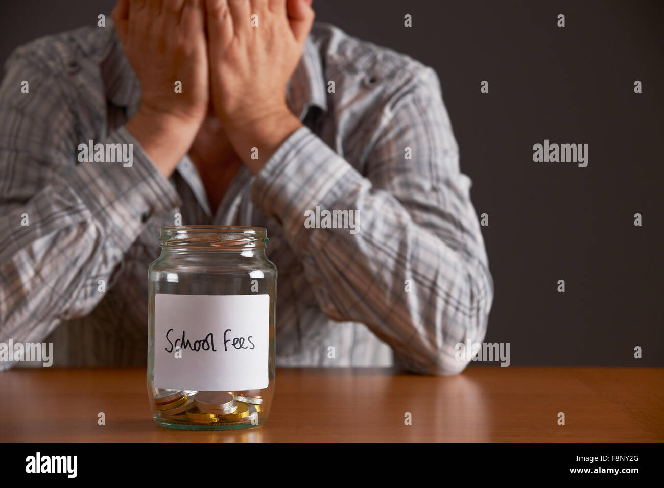 Man With Head In Hands Looking At Jar Labelled School Fees - Stock Image