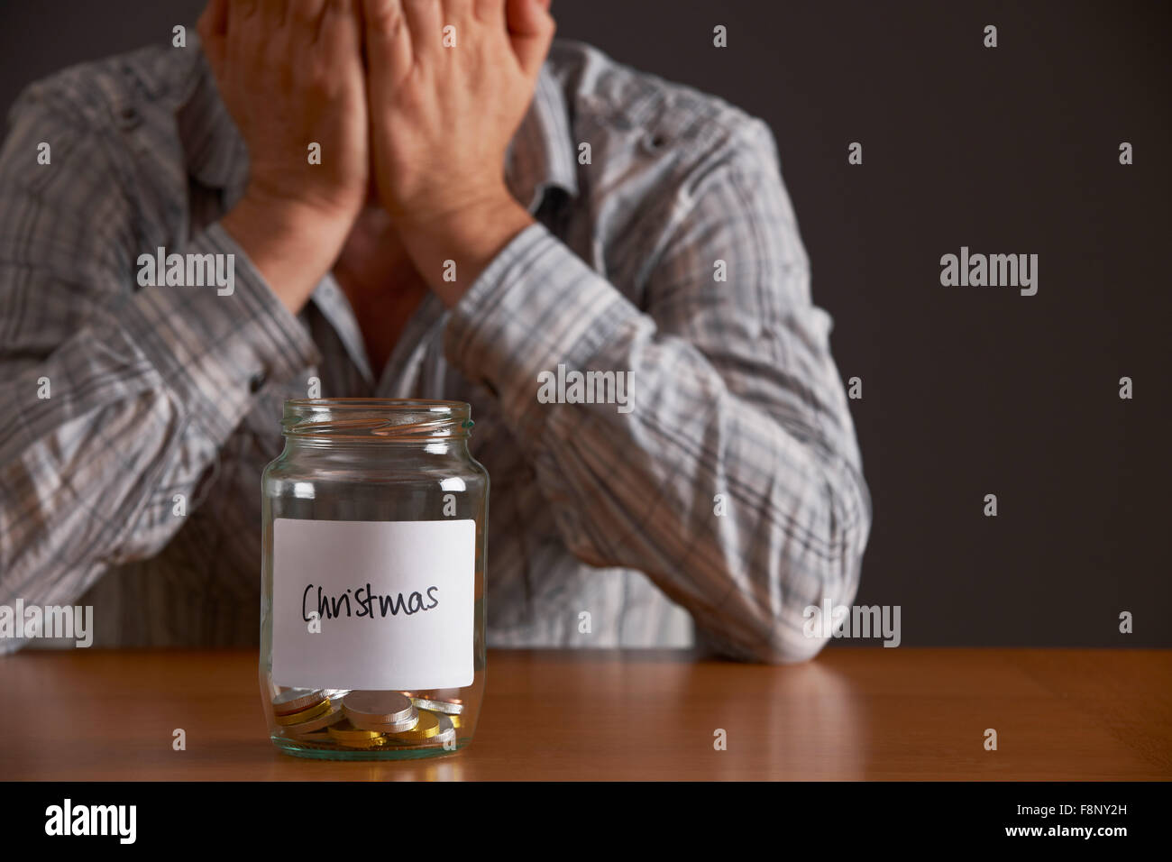Man With Head In Hands Looking At Jar Labelled Christmas Stock Photo
