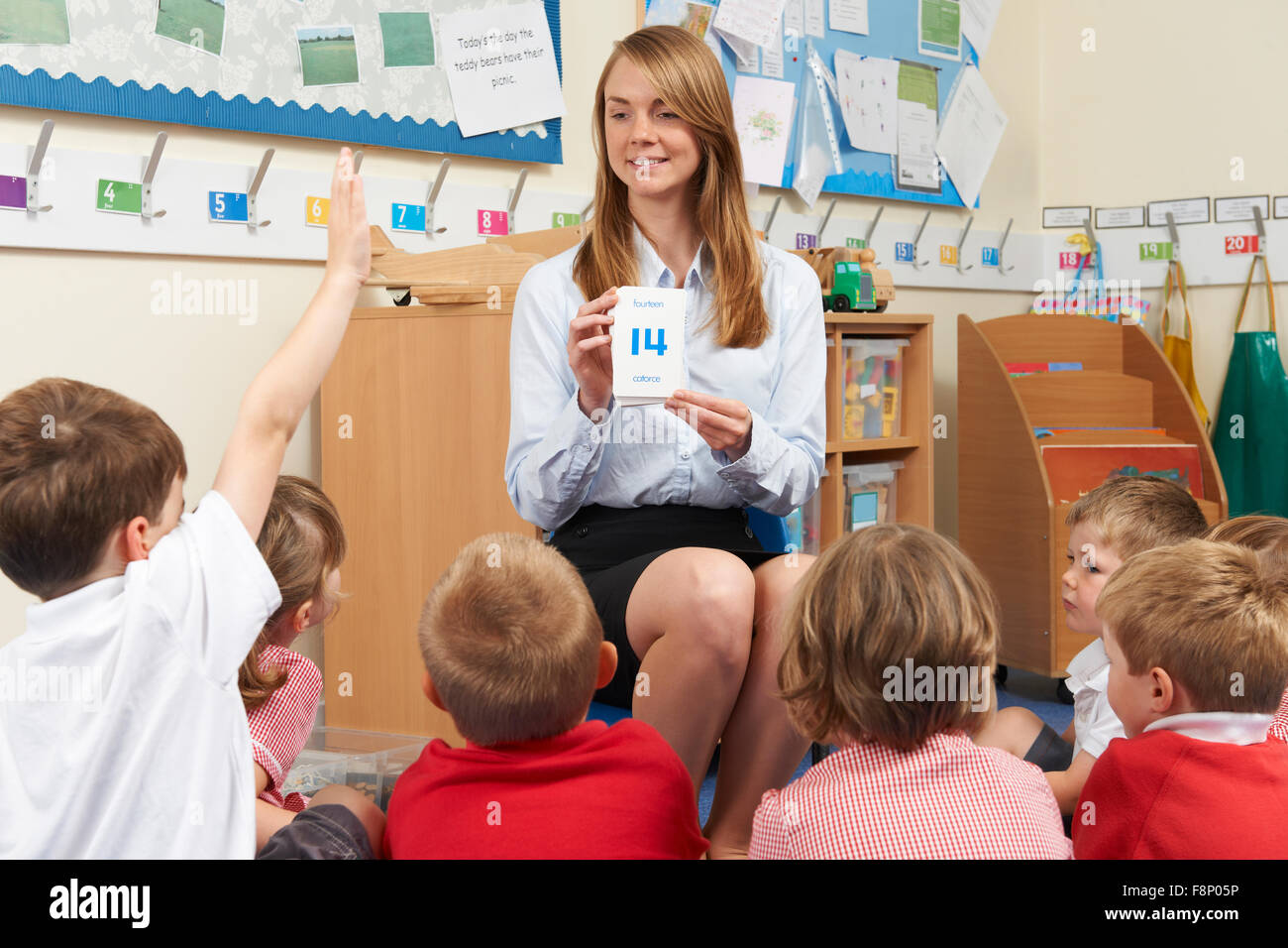 Teacher Using Flash Cards To Teach Maths To Elementary Class - Stock Image