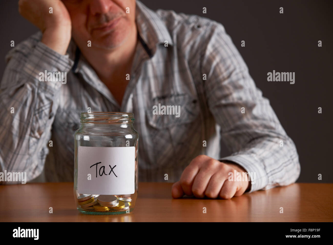 Depressed Man Looking At Empty Jar Labelled Tax Stock Photo