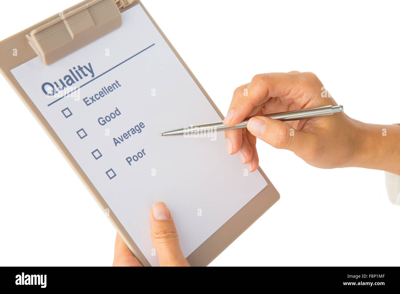 Woman's hand fills out quality checklist on white - Stock Image