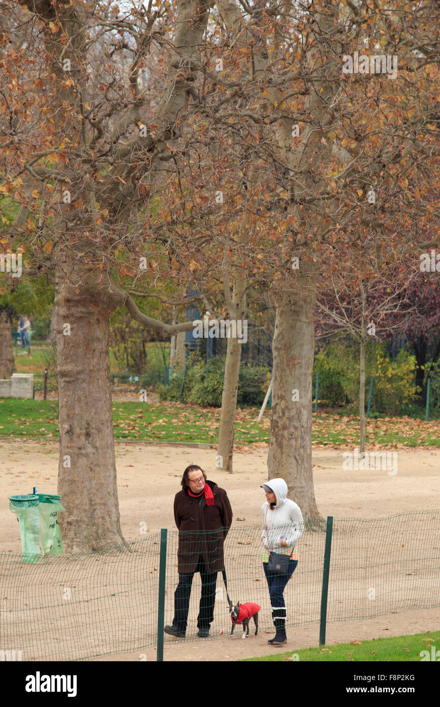 Locals walk their dog through a small park beside the Eiffel Tower in Paris, France. - Stock Image