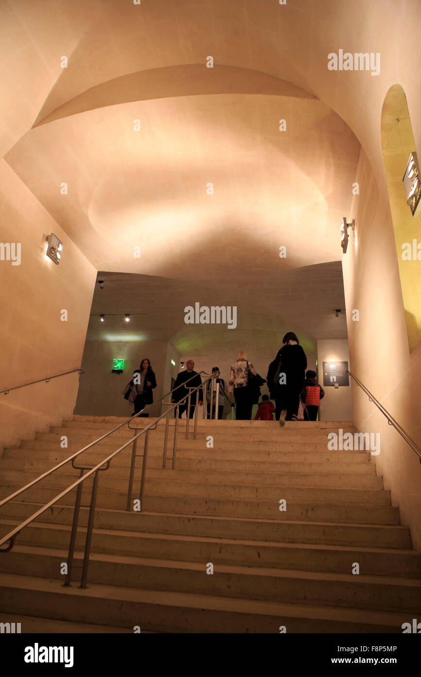 Visitors wander the stairs and hallways of The Louvre Museum, Paris, France. - Stock Image