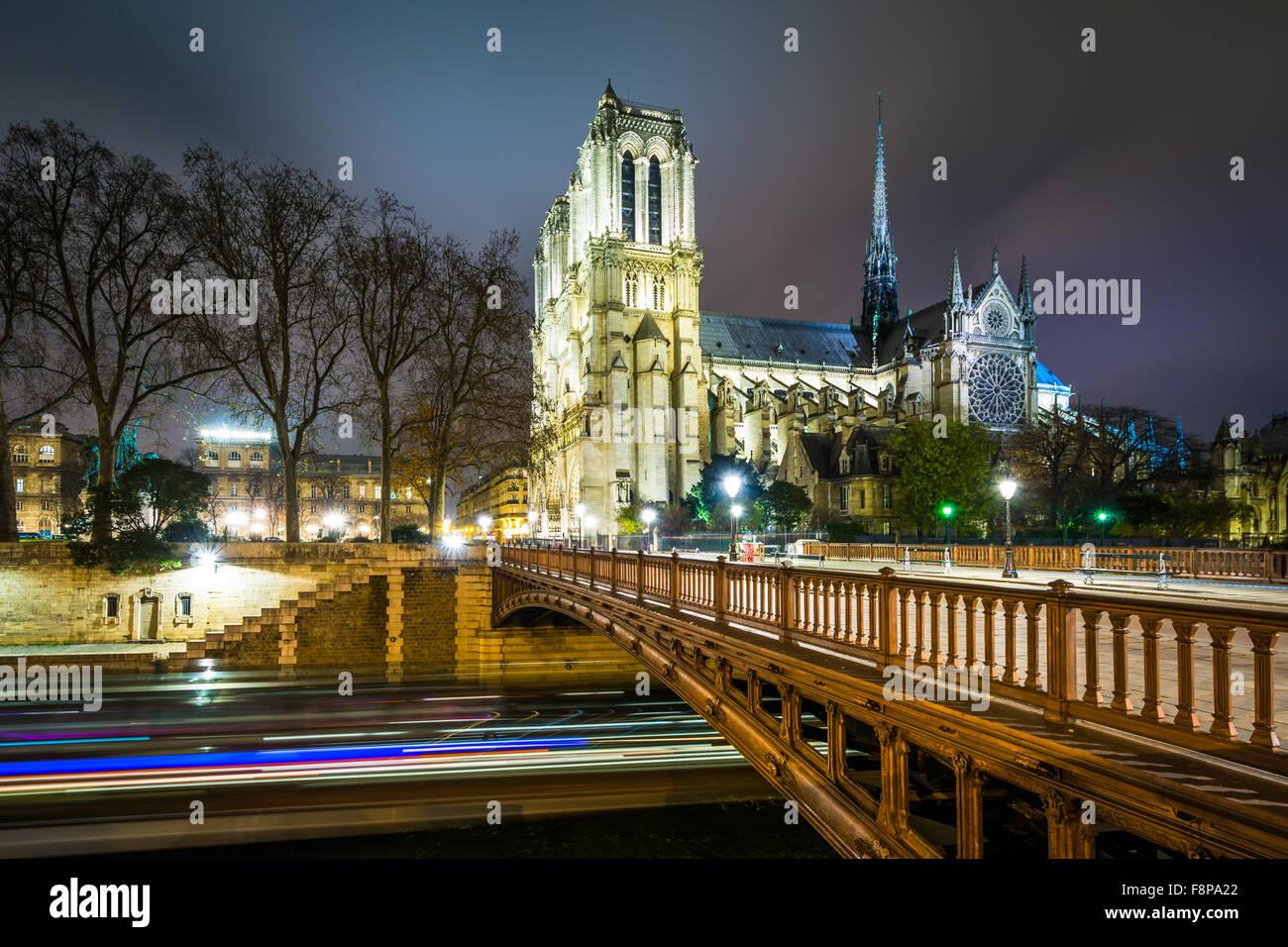 The Cathédrale Notre-Dame de Paris and Pont au Double at night, in Paris, France. - Stock Image