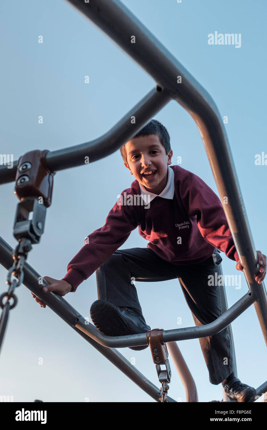 Schoolboy climbing in school playground - Stock Image