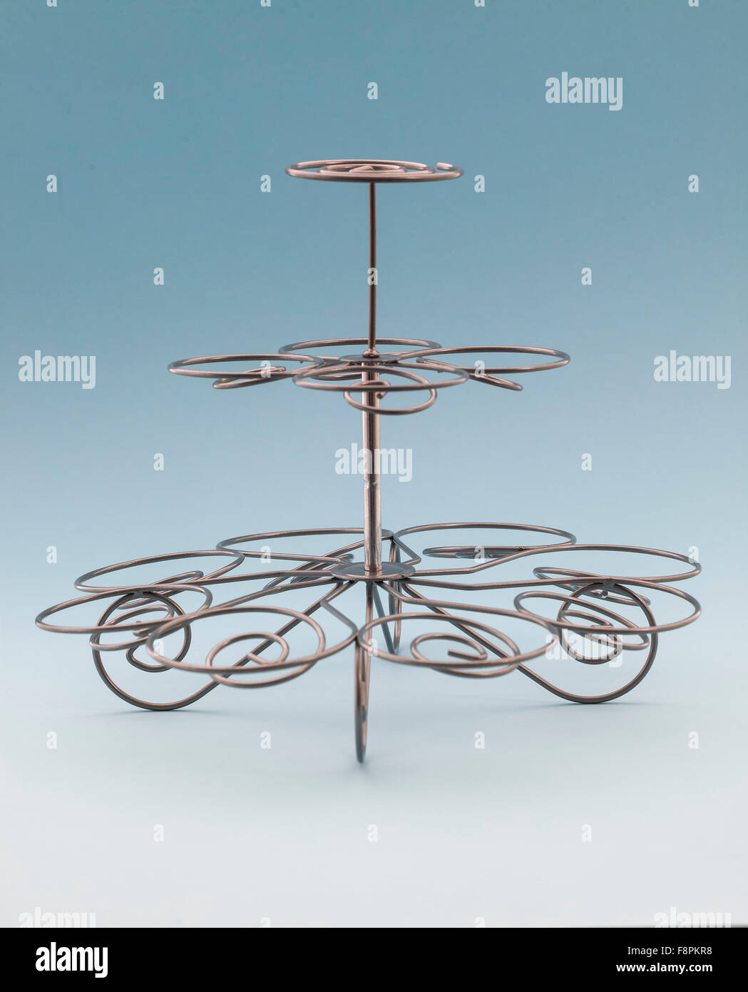Wire Cup Cake Stand on a Light Blue Background - Stock Image
