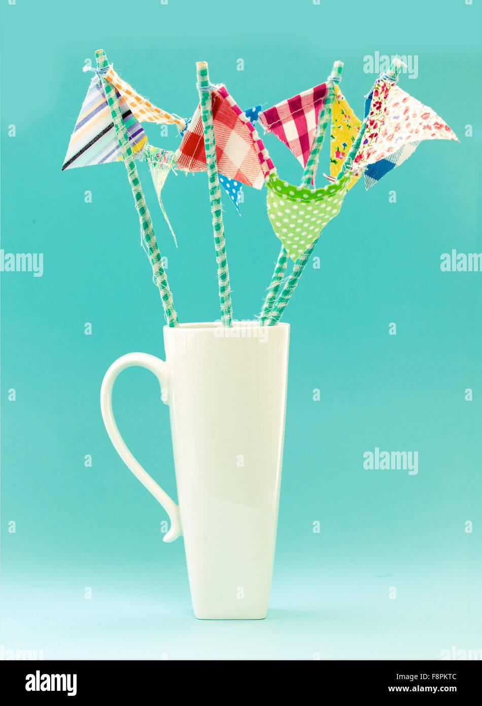 White Mug With Handmade Multicoloured Flags on a Turquoise Retro Background - Stock Image