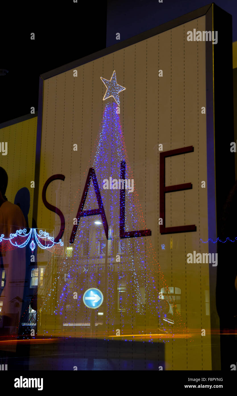 Christmas Tree Lights Reflecting On A Sale Sign In A Shop