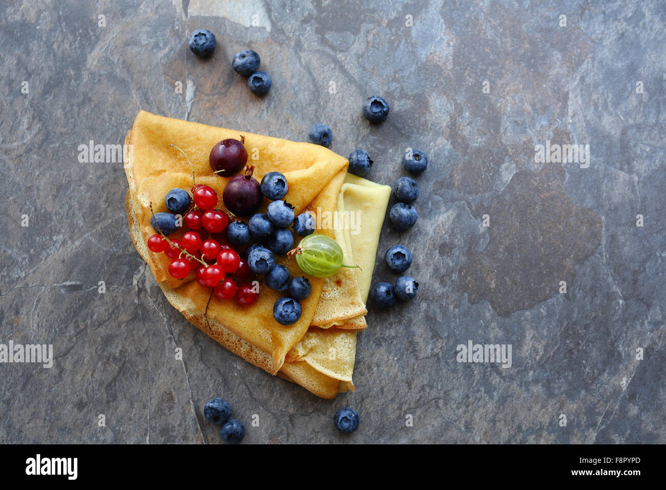 pancakes with berries on slate, food top view - Stock Image