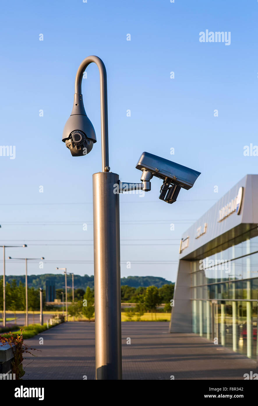 CCTV security camera under blue sky - Stock Image