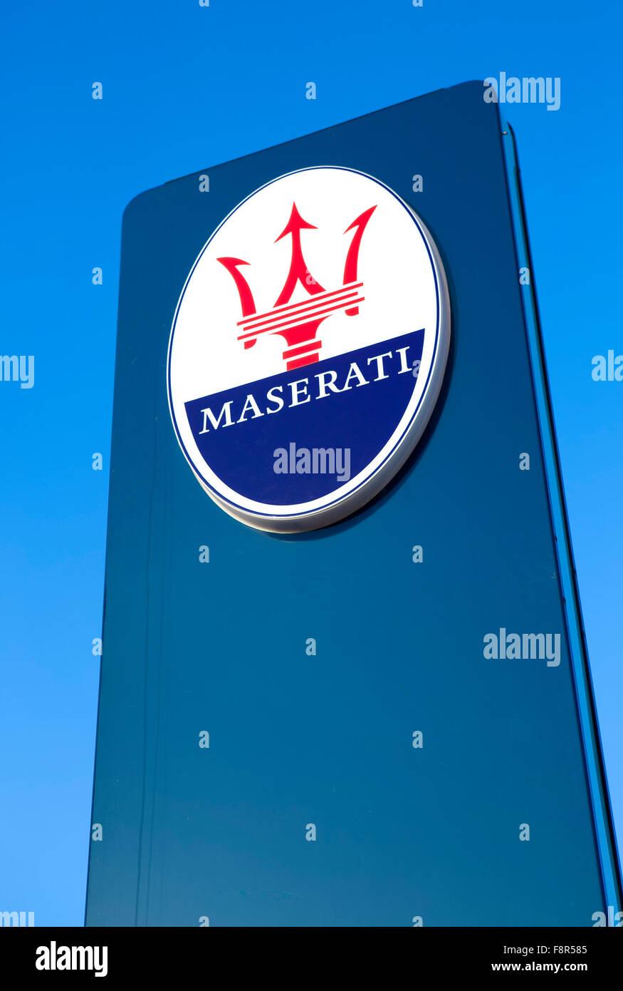 Maserati Sign Outside Car Dealership against a blue sky showing the logo of the Italian sports car producer 'Maserati' - Stock Image