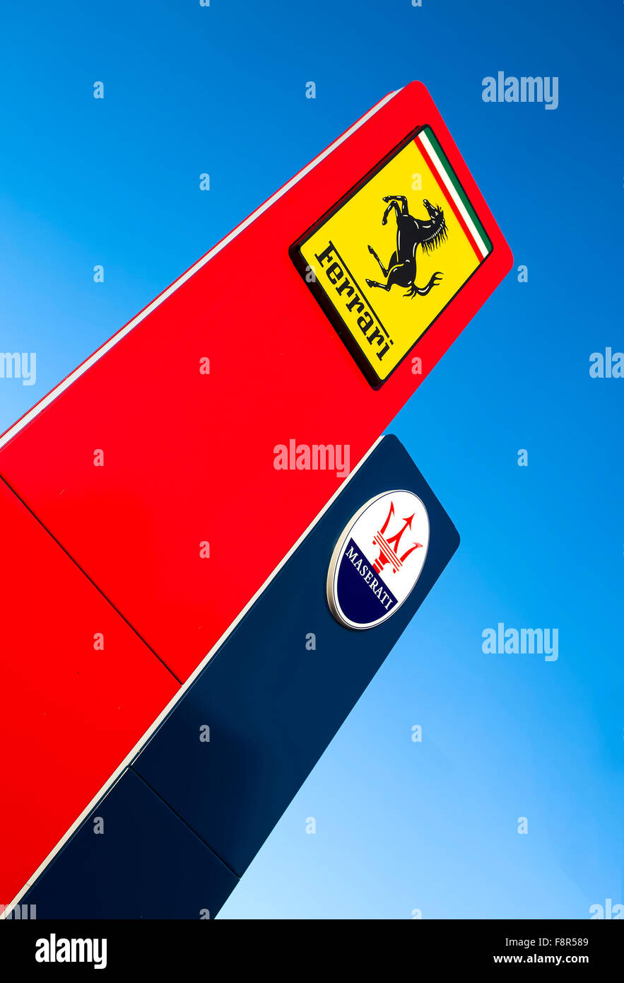 Maserati and Ferrari Signs Outside Car Dealership against a blue sky showing the logos of the Italian sports car - Stock Image
