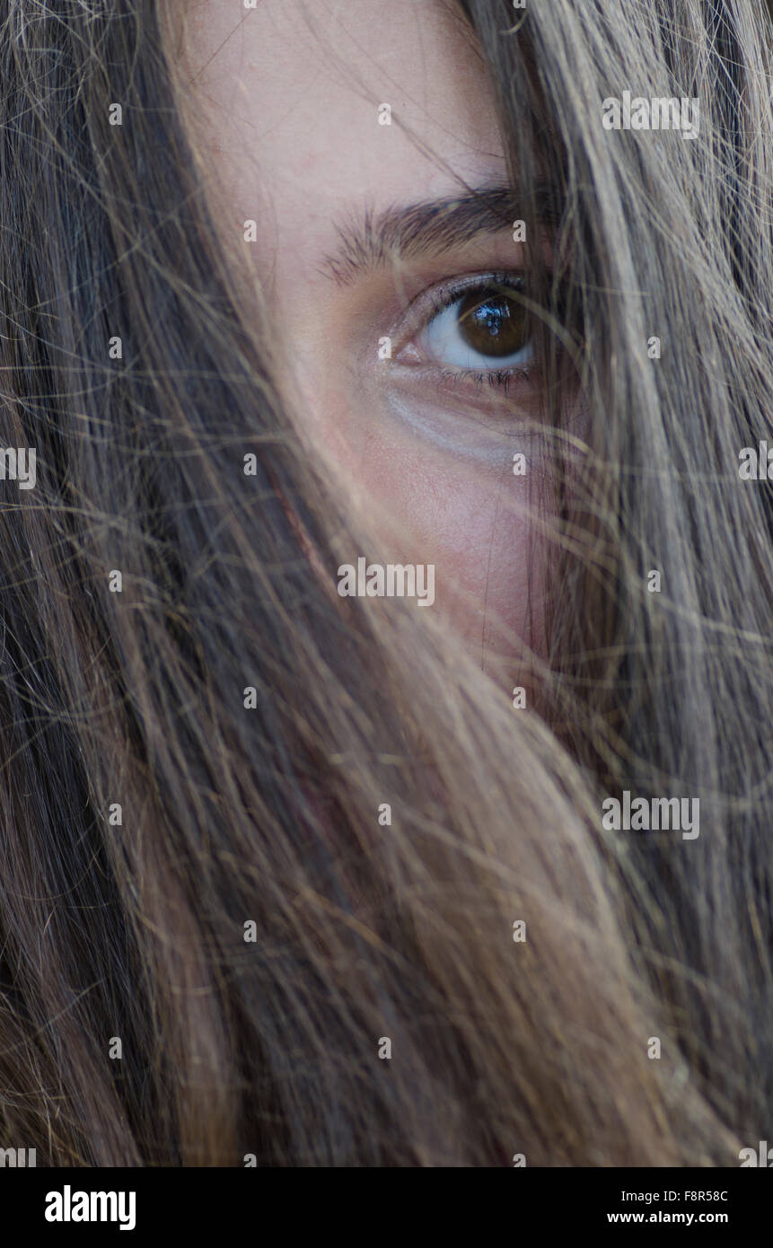Sad teenage girl hair covering face outdoors Stock Photo