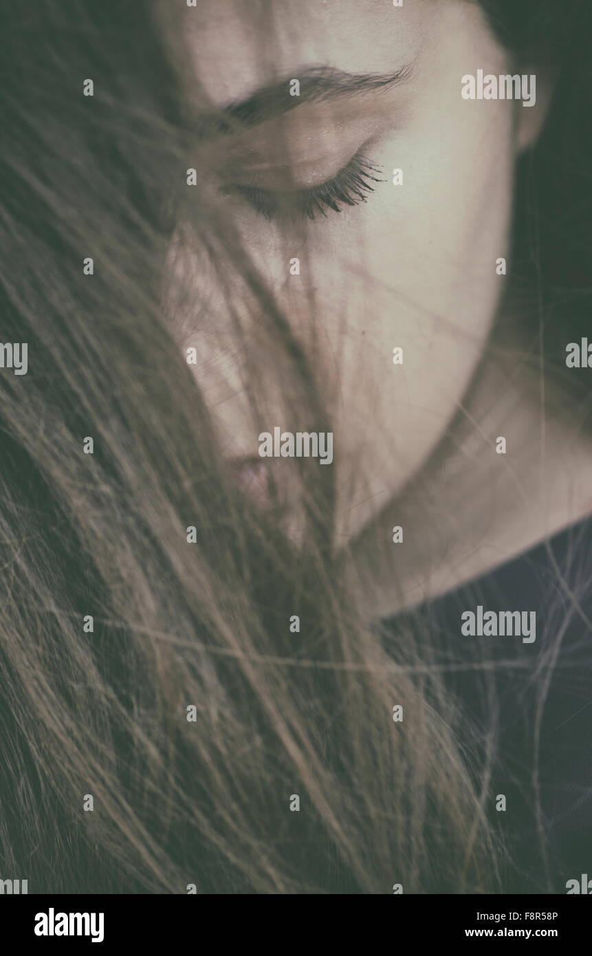 Sad teenage girl hair covering face outdoors - Stock Image