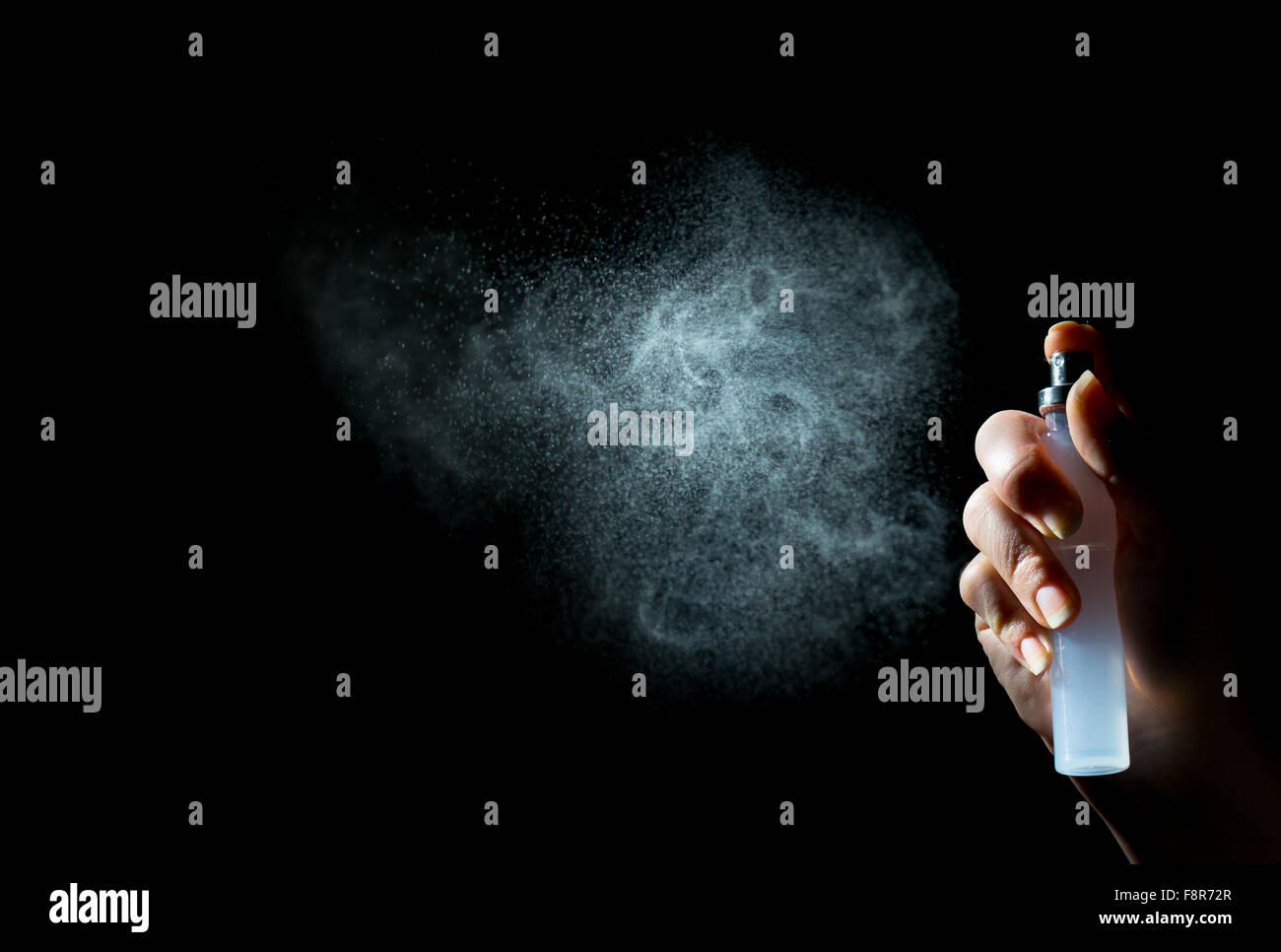 Blowing perfume in the form of small cloud particles - Stock Image