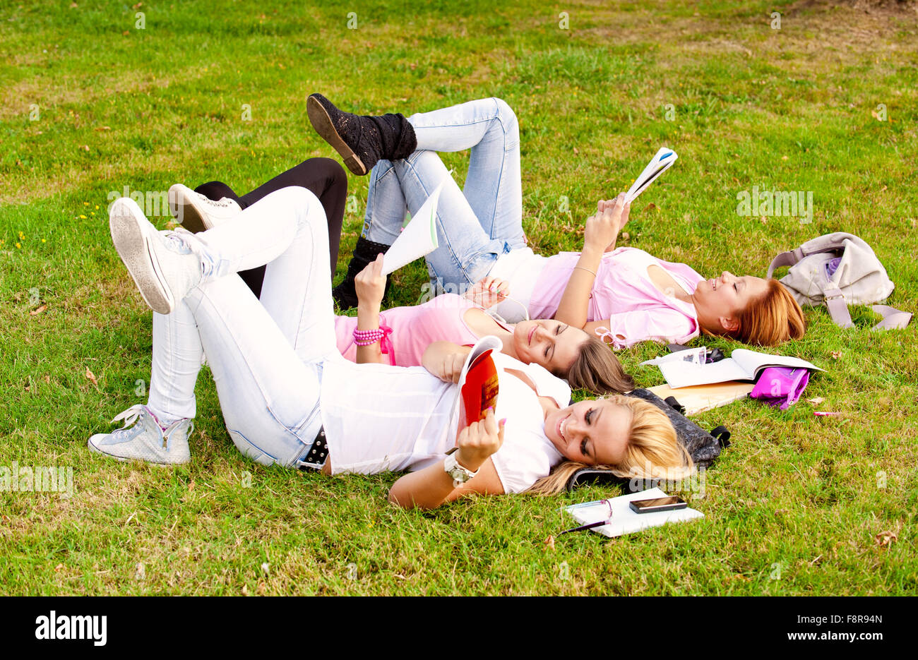 young college or high school student a break from learning on the grass in the park with his feet cocked in the - Stock Image