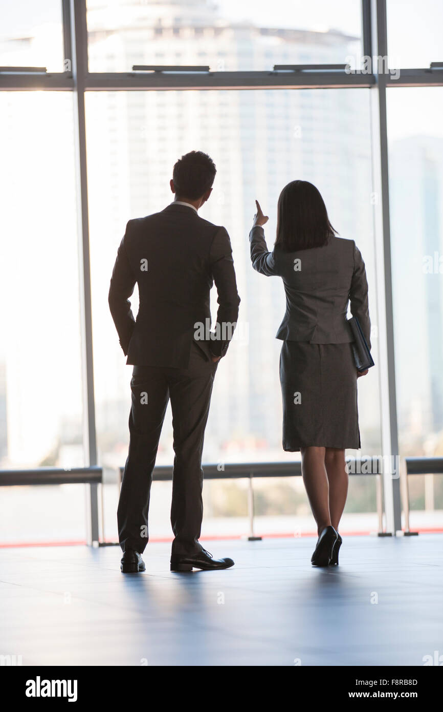 Business person looking through window - Stock Image