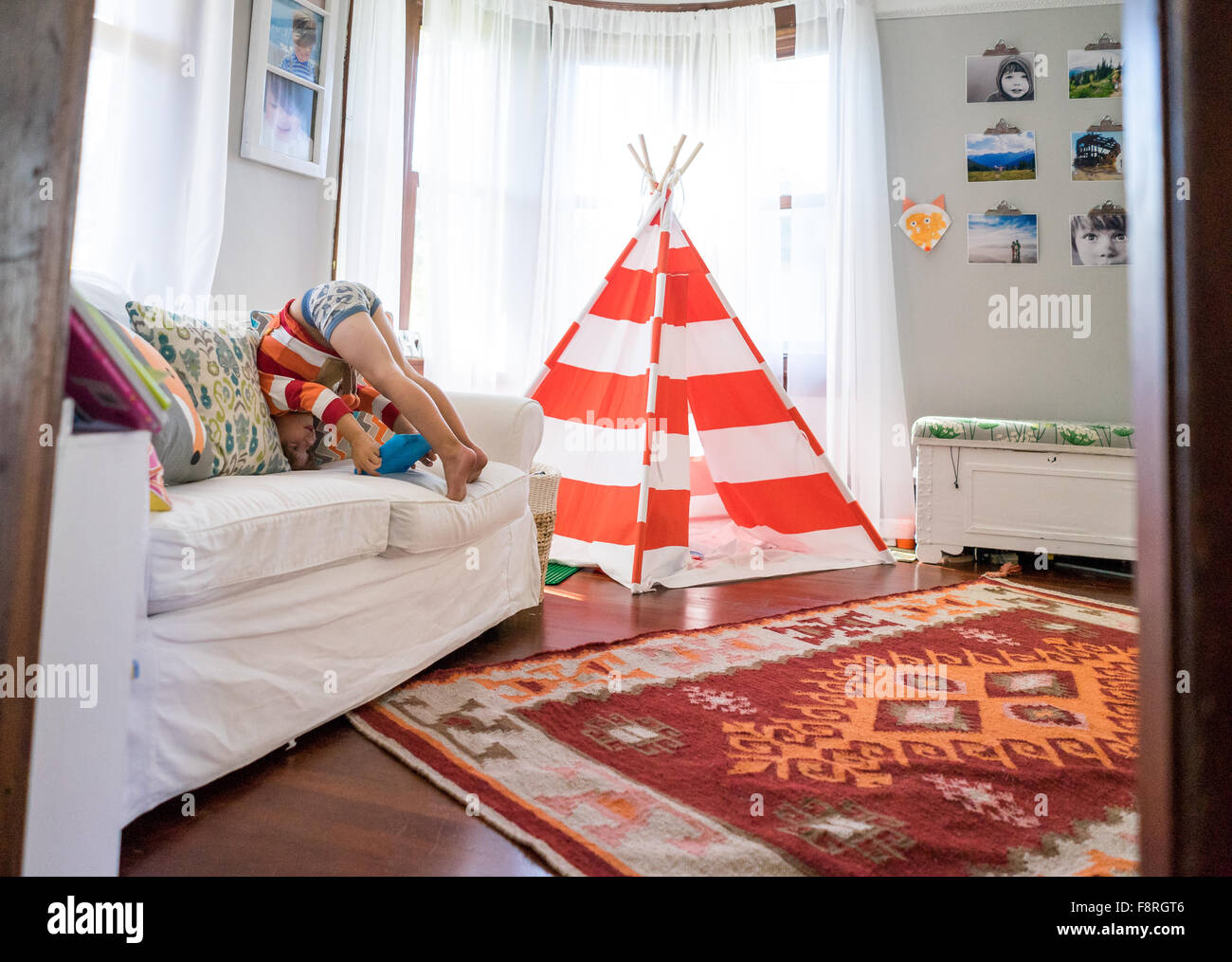 Young boy upside down  playing on tablet - Stock Image