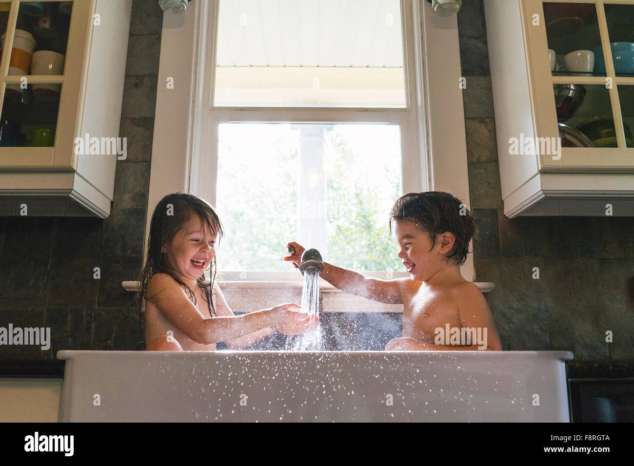 Young boy and girl sitting in kitchen sink playing with water - Stock Image
