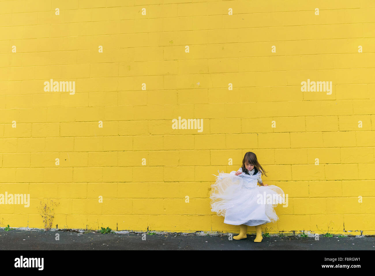 Girl twirling in dress by yellow wall - Stock Image