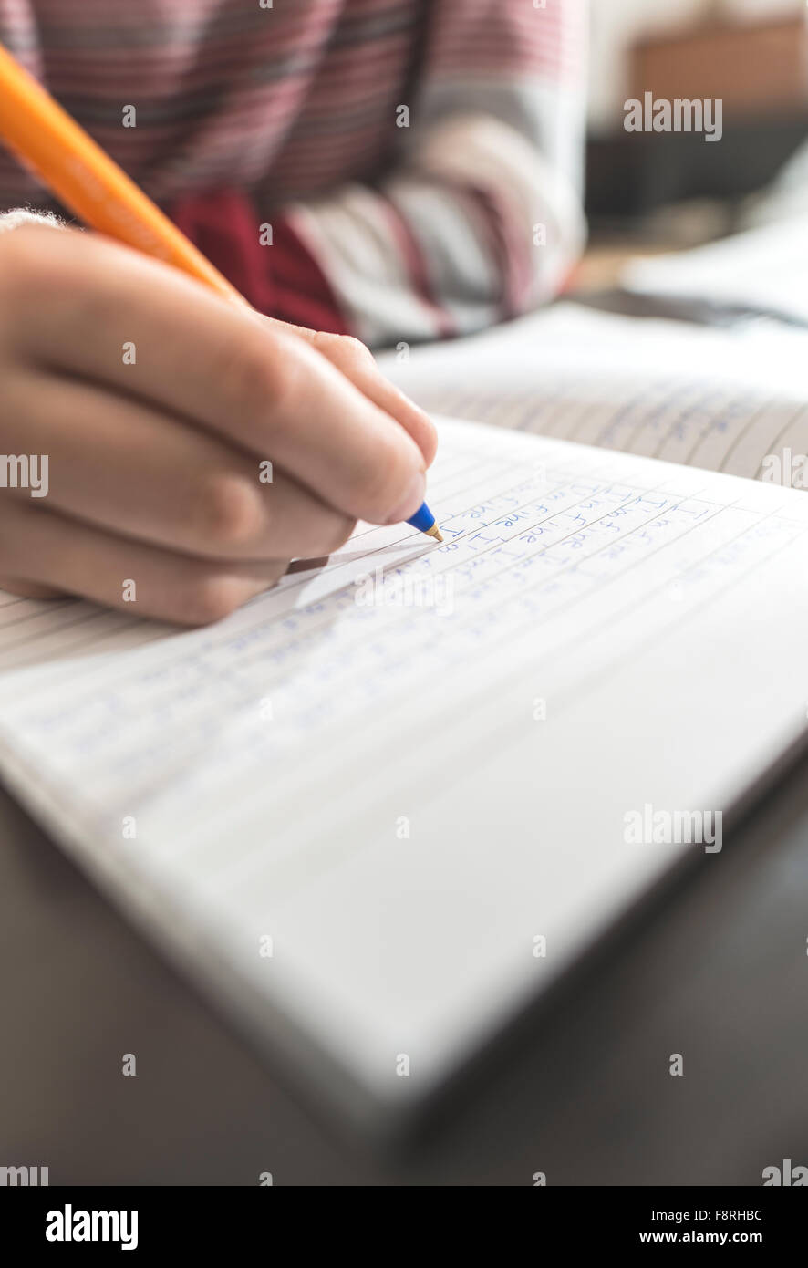 Boy writing in a notebook - Stock Image