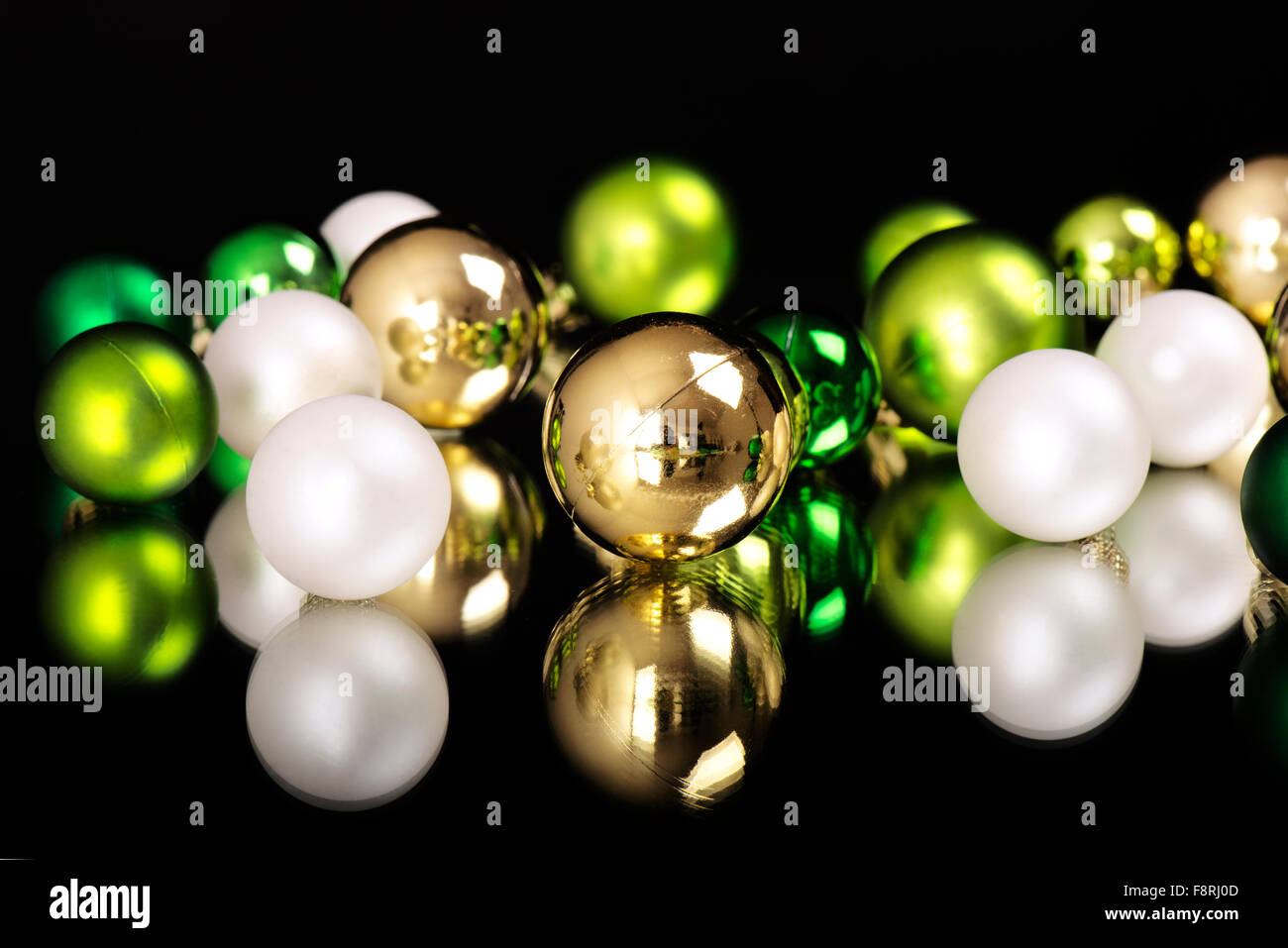 New Years And Christmas Ornaments Balls Of White Gold Green On A Mirror In Front Black Background