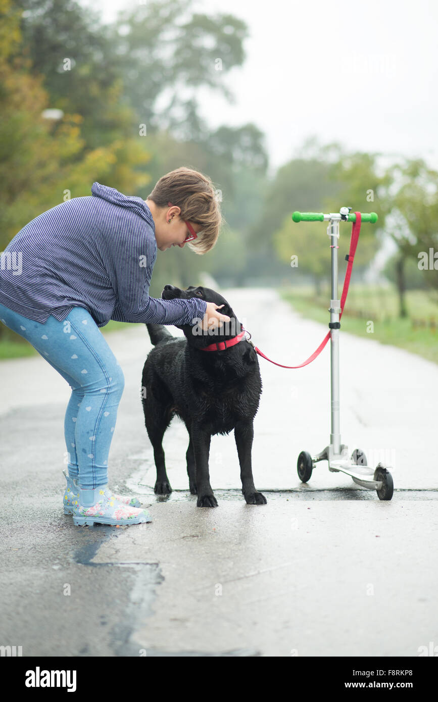 Girl stroking dog tied to push scooter Stock Photo