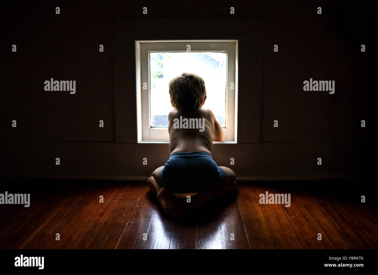 Boy sitting on floor looking out of a window - Stock Image