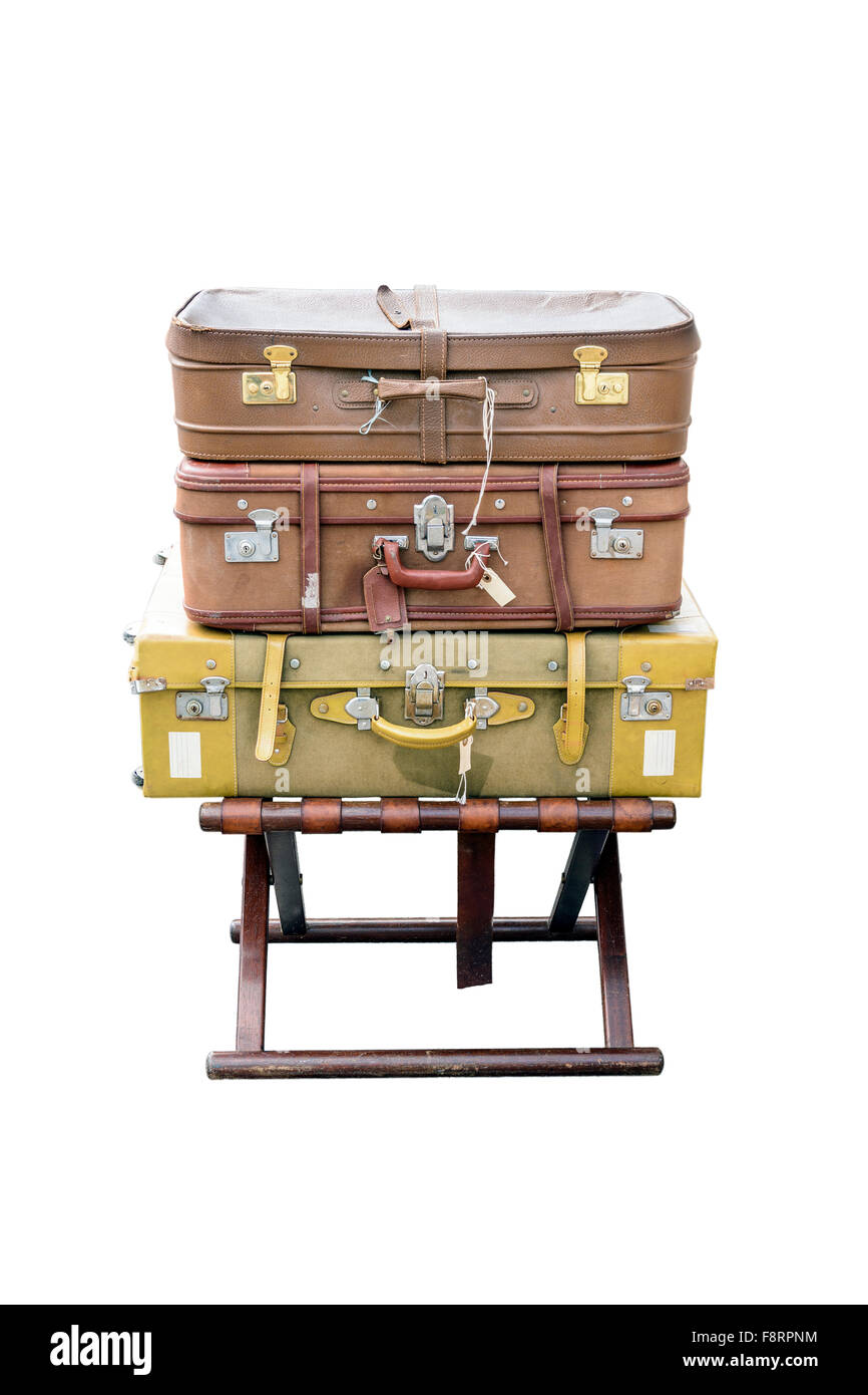 Old suitcases travel resting on a wooden stool and isolated on white background. - Stock Image