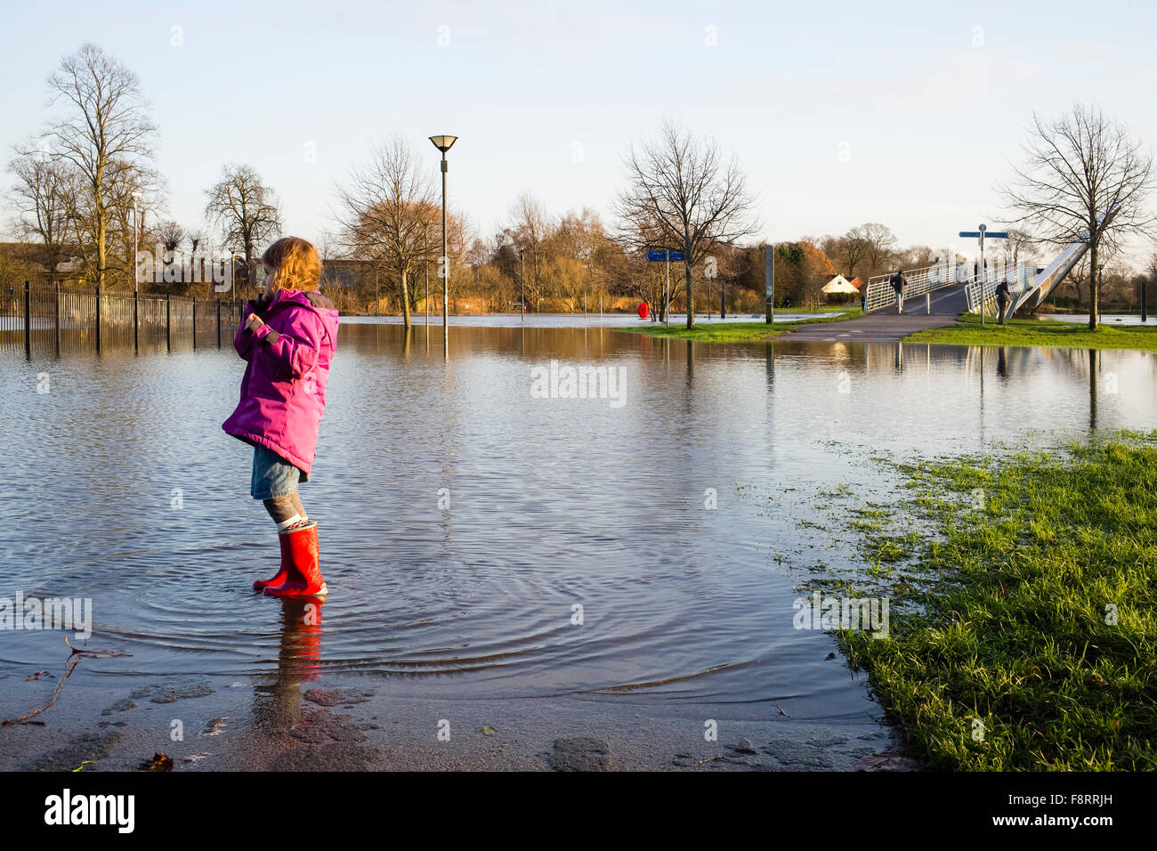 Girl in red boots reflected in floodwater, River Ouse, City of York, Yorkshire, England, UK Stock Photo