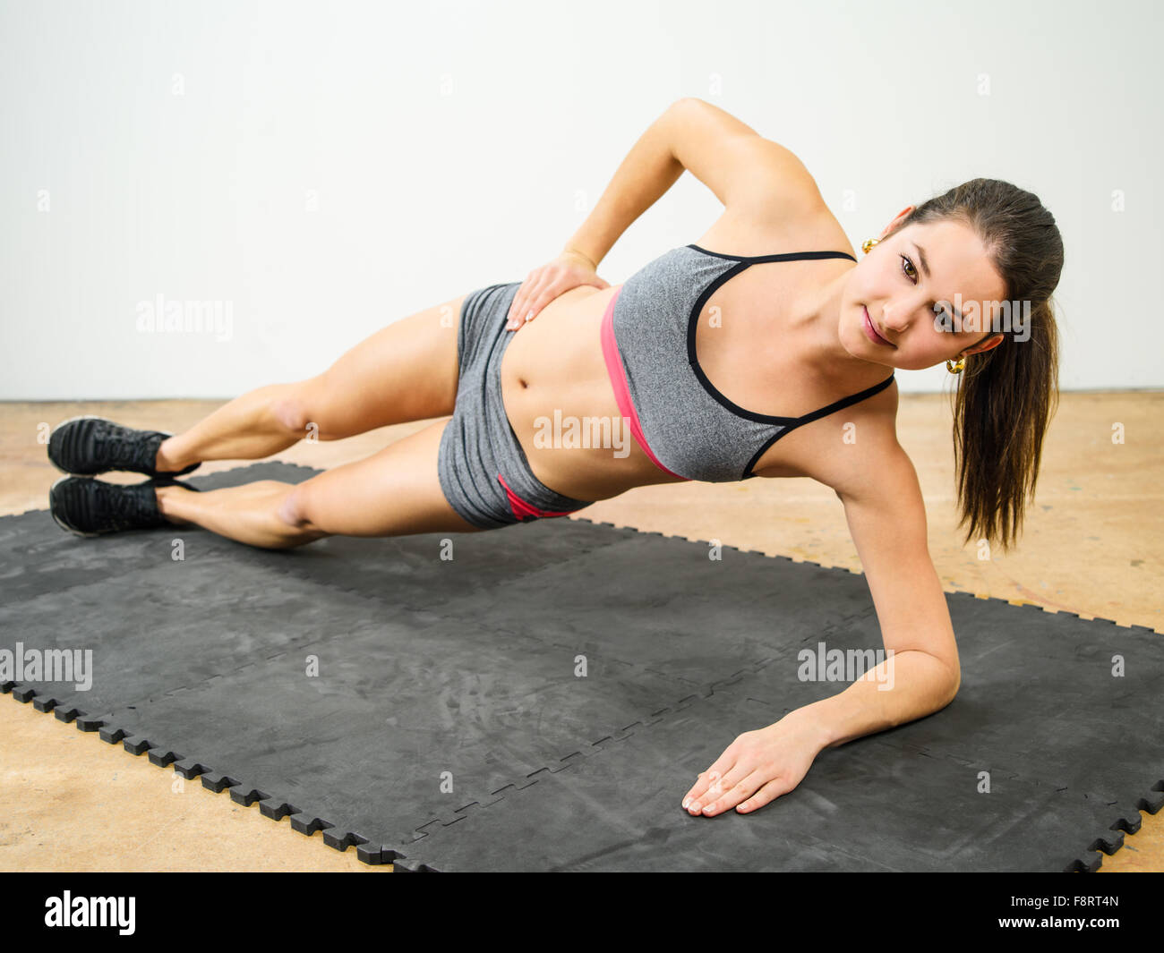 Photo of a young woman in her twenties doing a side elbow plank. - Stock Image