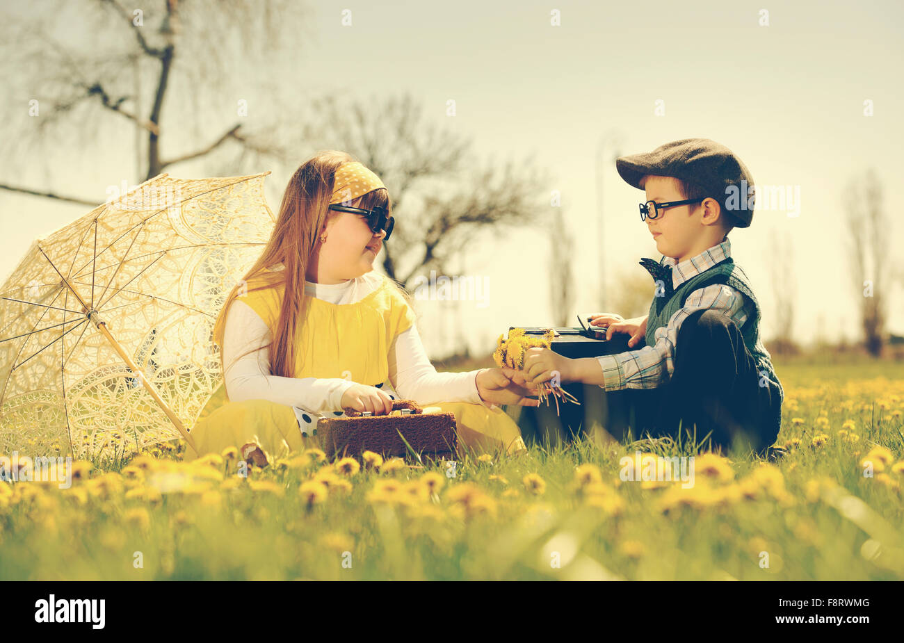 little boy courting a girl of the park in a flower meadow.vintage-look - Stock Image