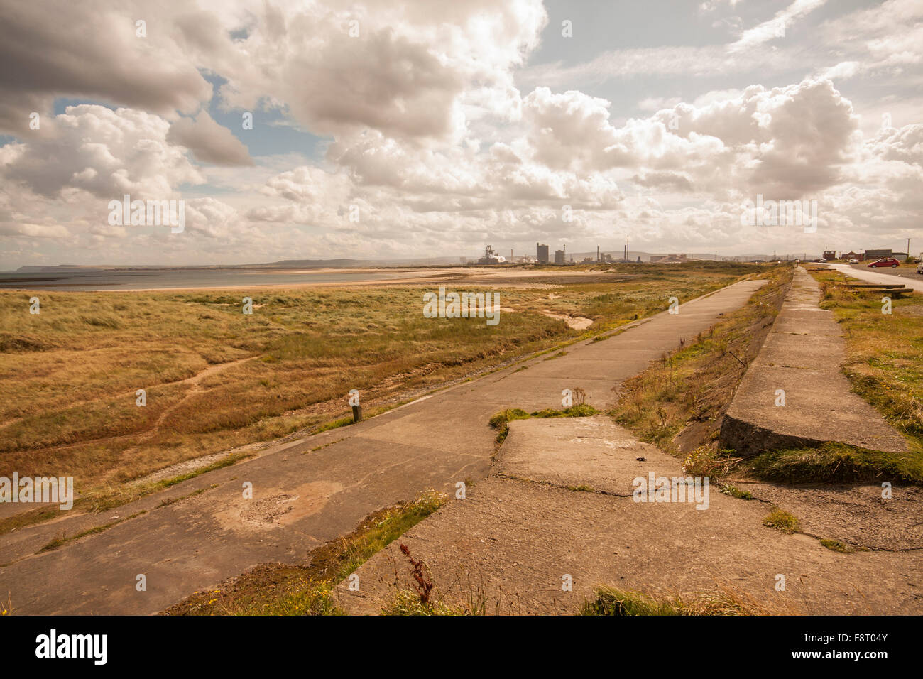 A view of the rugged north east coastline at Redcar showing the former blast furnace works and cloudy blue skies - Stock Image