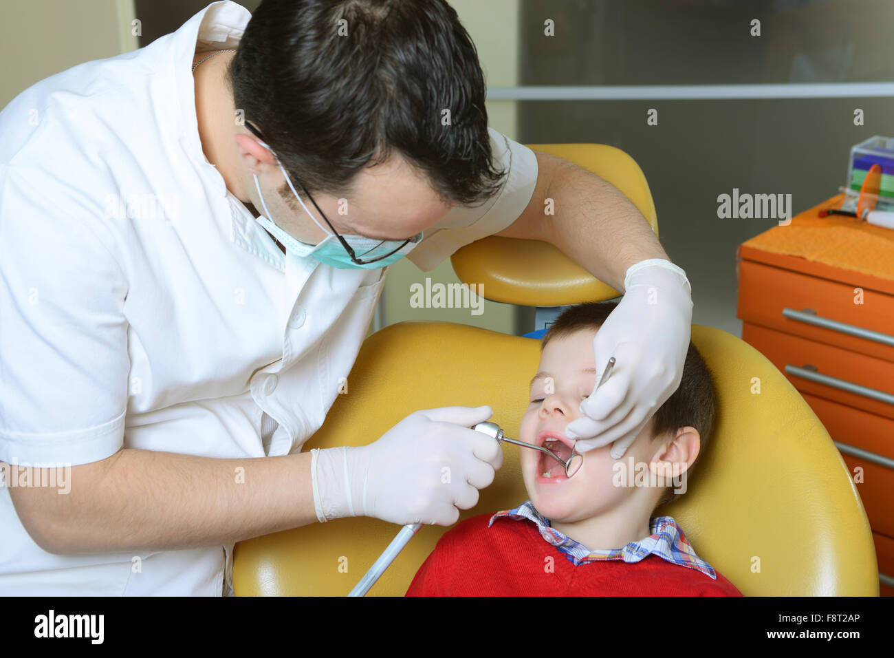 little boy in a red sweater went to the dentist in the dental chair sits next to a doctor to do the dentist to see - Stock Image