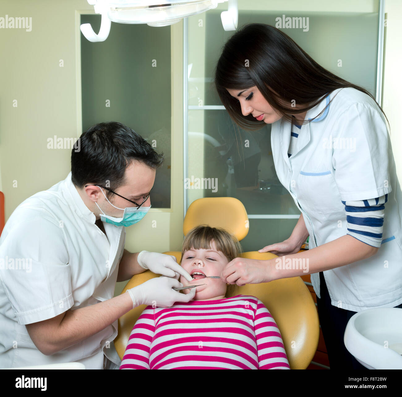little girl to the dentist in the dental chair sits next to a doctor to do the dentist to see if his teeth were - Stock Image