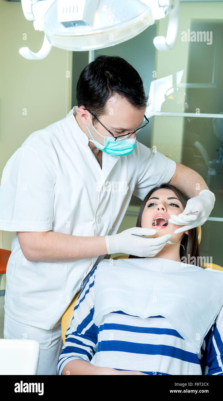 young women to the dentist in the dental chair sits next to a doctor to do the dentist to see if his teeth were - Stock Image