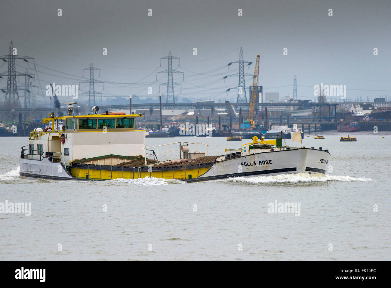 The general cargo ship, Polla Rose steams upriver on the River Thames. - Stock Image